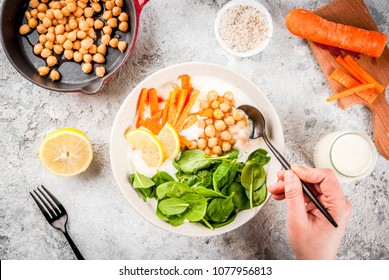 Modern vegan food, person eat  savory yogurt bowl with beans, chickpeas, spinach, spicy carrots, lemon, Gray stone background, copy space top view, hands in picture