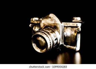 A modern version of a camera in silver and gold with black background