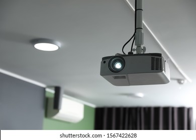 Modern video projector on ceiling in room