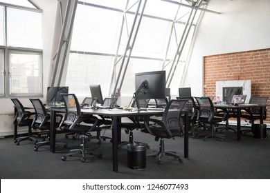 Modern view of empty office space interior, open plan office concept, trendy loft workspace with big windows, lot of office equipment, computers, monitors, natural light, creativity, without people