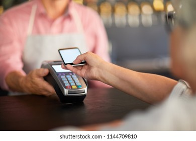 Modern visitor paying through mobile payment system in smartphone after eating in cafe