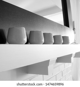 Modern votive candle holders on fireplace mantle with mirror