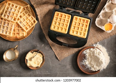 Modern waffle maker with ingredients on grey table