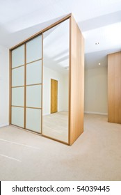 Modern walk in cloakroom with large floor to ceiling wooden wardrobes with slide doors