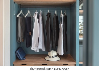 modern walk in closet with clothes hanging on rail, modern wardrbe with shirts hanging, interior design concept
