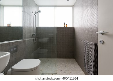 Modern walk in shower with mosaic full height tiles and terrazzo floor