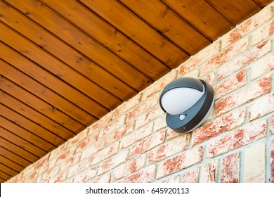Modern wall lamp with motion and light sensor on the brick wall - pathway or wall light for modern design building or house - motion activated porch light - part of home security system