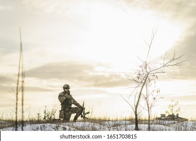Modern war soldier army man in the winter multicam camouflage is patrolling or patrol field territory. full equipment commandos with helmet and weapon gun. soldier crouching on one leg in winter field