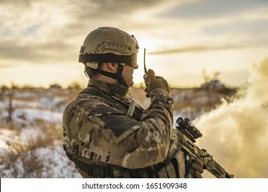 Modern war soldier army Man in multicam camouflage speaks on the walkie-talkie radio. equipment commandos with helmet and gun. soldier, sun backlight and smoke. modern warfare. atmosphere of battle.