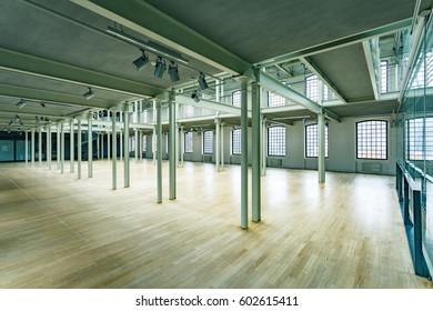 Modern warehouse interior with windows, wood floor and pillars