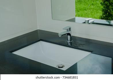 Modern wash basin in the bathroom, chrome faucet in the ceramic wash basin in the bathroom
