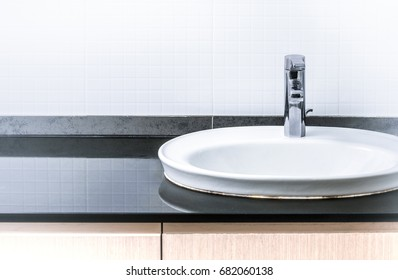 Modern wash basin in the bathroom. There is a ceramic wall.