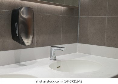 Modern wash hand basin with hand free sensor tap and soap dispenser. Solid Surface worktop and grey tiled wall.