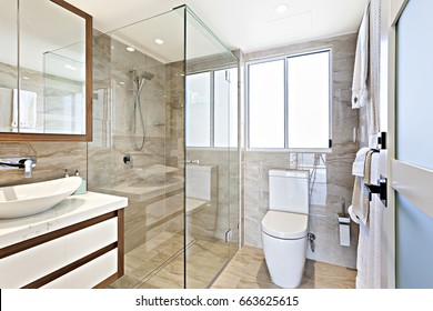 Modern wash room with all facilities, very comfortable  look, perfect lights, glass door can see near walls, ceramic items are shiny