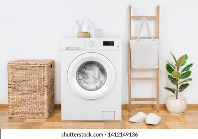 Modern washing machine with basket in laundry room interior