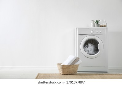 Modern washing machine and laundry basket near white wall indoors, space for text. Bathroom interior