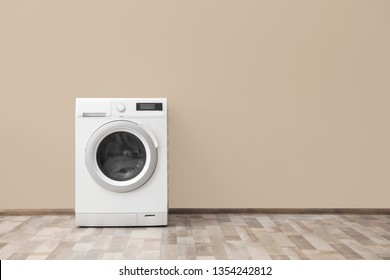 Modern washing machine with laundry near color wall, space for text