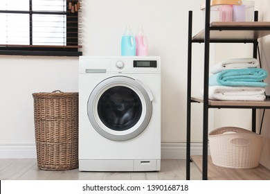 Modern washing machine in laundry room interior