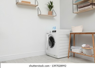 Modern washing machine in laundry room interior. Space for design