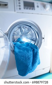 Modern washing machine loaded with blue towel