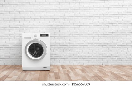 Modern washing machine near brick wall in empty laundry room, space for text