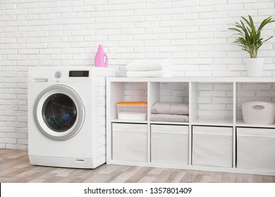 Modern washing machine near brick wall in laundry room interior