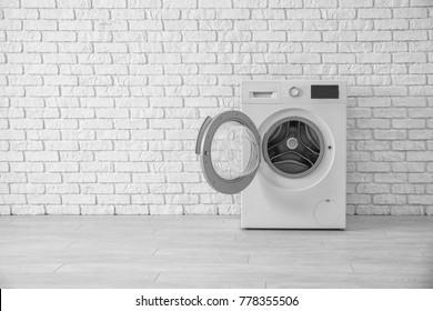 Modern washing machine near brick wall