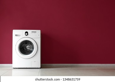 Modern washing machine near color wall