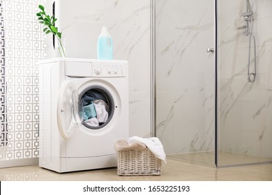 Modern washing machine with towels in bathroom