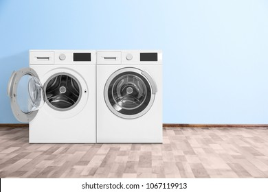 Modern washing machines near color wall indoors. Laundry day