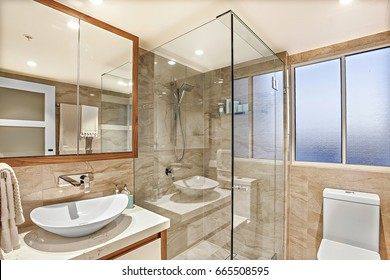 Modern washroom, shower area and washing area, including a white sink and silver taps on the ceramic counter beside glass cover and the toilet bowl, the mirror is attached to the wall