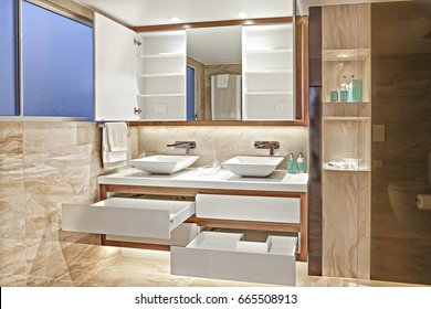 Modern washroom with soap cabinet and white wood drawers under the wall mirror, there is a white ceramic wash basin with silver tops