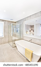 Modern washroom with space and tile floor with walls, including a white washbasin with a yellow towel under the window, the shower area has a reflective glass cover