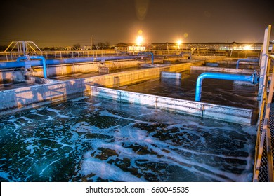 Modern wastewater treatment plant of chemical factory at night. Water purification tanks