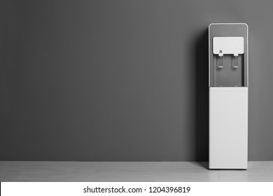 Modern water cooler against gray wall with space for text