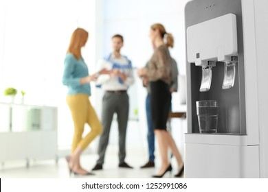 Modern water cooler with glass and blurred office employees on background. Space for text