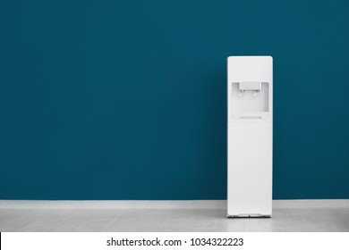 Modern water cooler near color wall