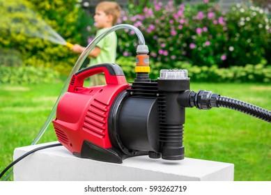 Modern water pump in the garden on a hot summer day