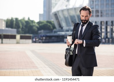 Modern way of life. Professional handsome businessman checking time while standing in the city