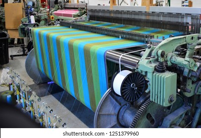 A modern weaving machine creating a colorful fabric