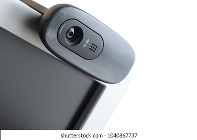 A modern web camera is installed on the body of a flat screen monitor. Device for video communication and recording of high quality video
