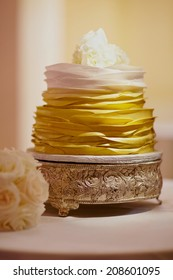 Modern wedding cake on reception table with dramatic lighting