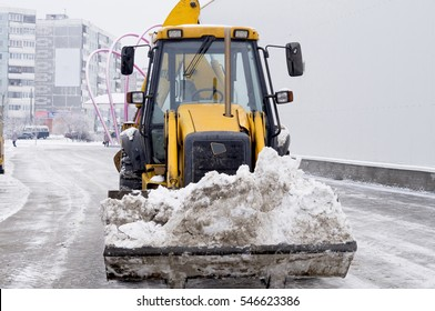modern wheel loader clearing snow in the city