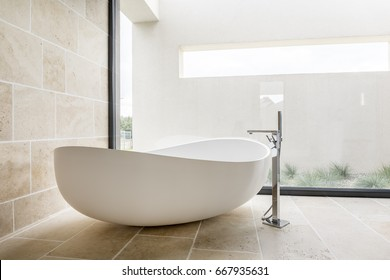 Modern white bathtub in spacious bathroom with glass wall