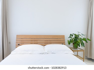 Modern white bedroom interior decorated with green Philodendron plant on bedside table