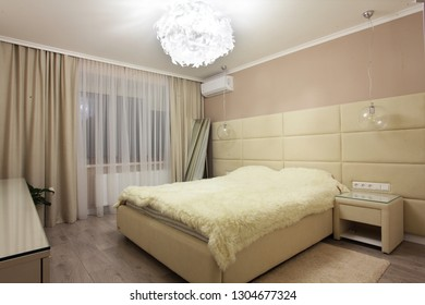 Modern white and beige bedroom with double bed.