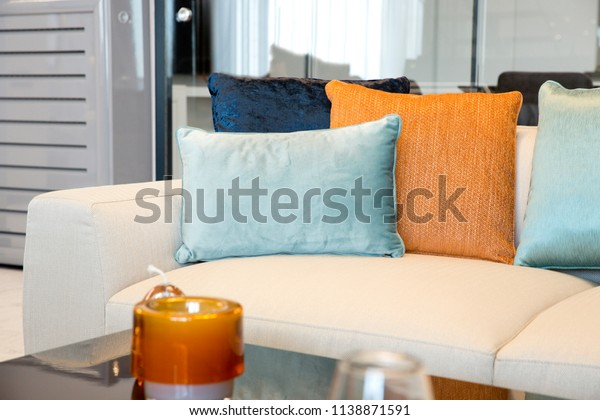 Modern white beige couch, light blue, dark blue and orange colored pillows. Black coffee table and glasses. Contemporary interior of modern designed Living room with part of sofa.