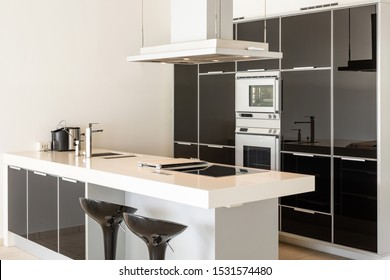 Modern white and black kitchen detail with island and stools. Stainless steel hood.