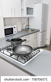 Modern white and black kitchen, gas stove with pan and pot, minimalistic clean design