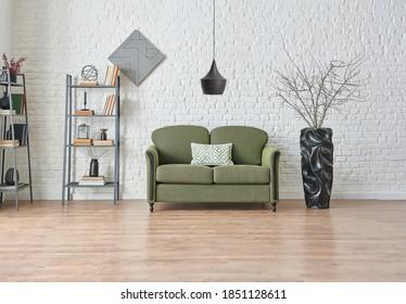 Modern white brick wall background, green and grey sofa, black furniture detail, working table with bookshelf.
